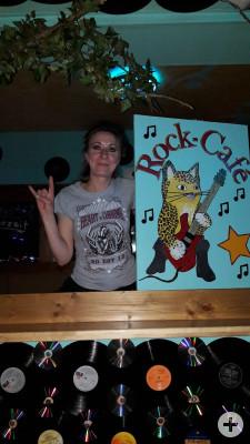 Die Wirtin mit einem der Kunstwerke aus dem Rockcafe